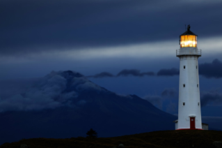 lighthouse-at-night-with-mountain-as-background