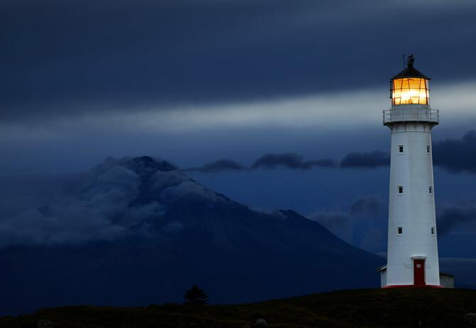 Implementing Operational Resilience in a Complex Insurance Ecosystem - lighthouse-at-night-with-mountain-in-background