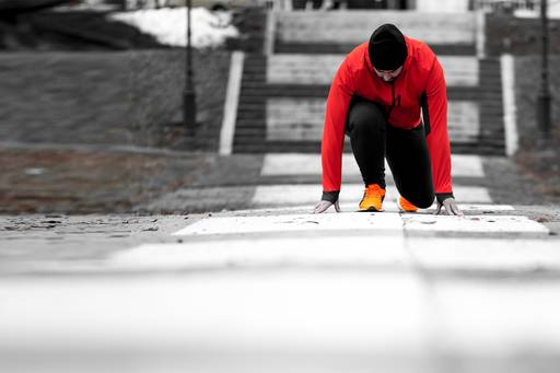 Male runner wearing a red jacket crouched in a starting position