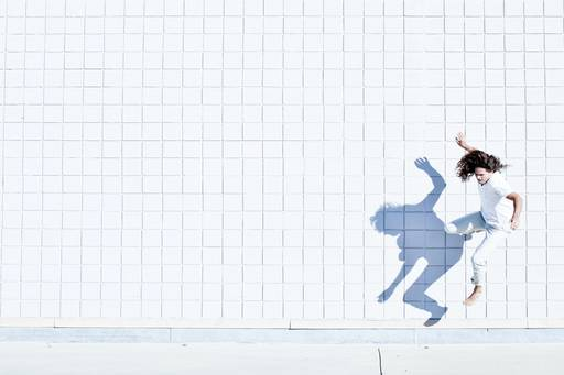 Man doing parkour on a white tiled background