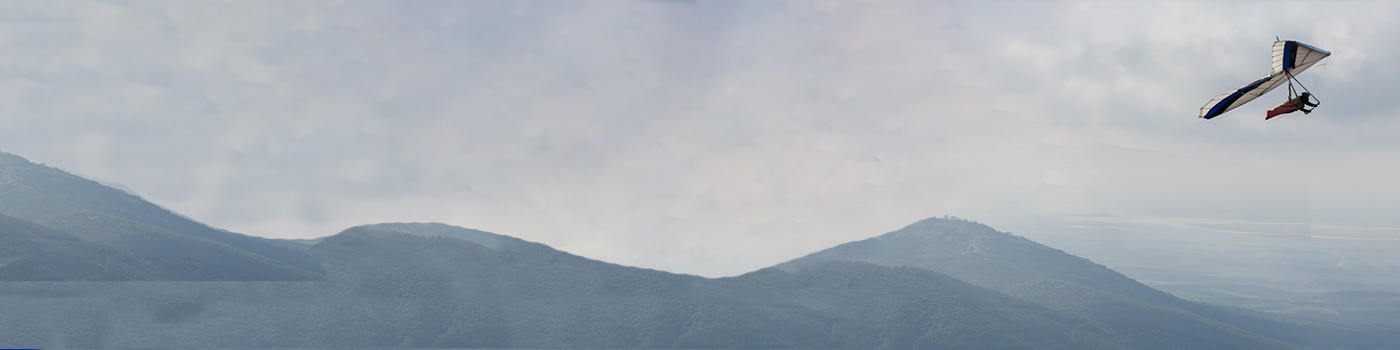 Person paragliding over foggy mountains