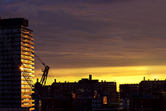 A high rise building being constructed at sunset
