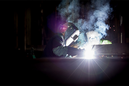 Two welding workers working at night