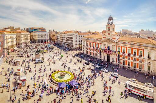 Crowded street with a round about in middle decorated with fountain and yellow flowers