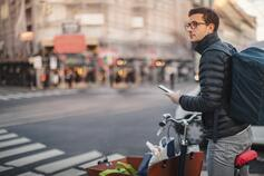 Man on bike with bag and phone