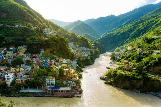River flowing across the mountains and colourful houses