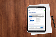 Tablet with KPMG site opened in browser, kept along with a paper and pen on a wooden background