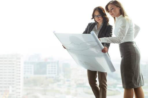 Two women standing by a window reading blueprints