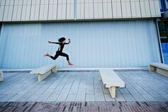 Woman jumping over benches