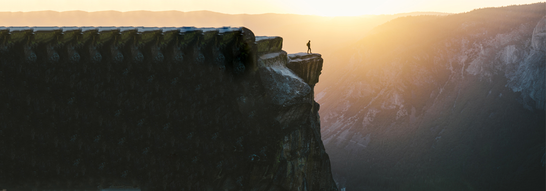 Hiker standing on mountain cliff during sunrise