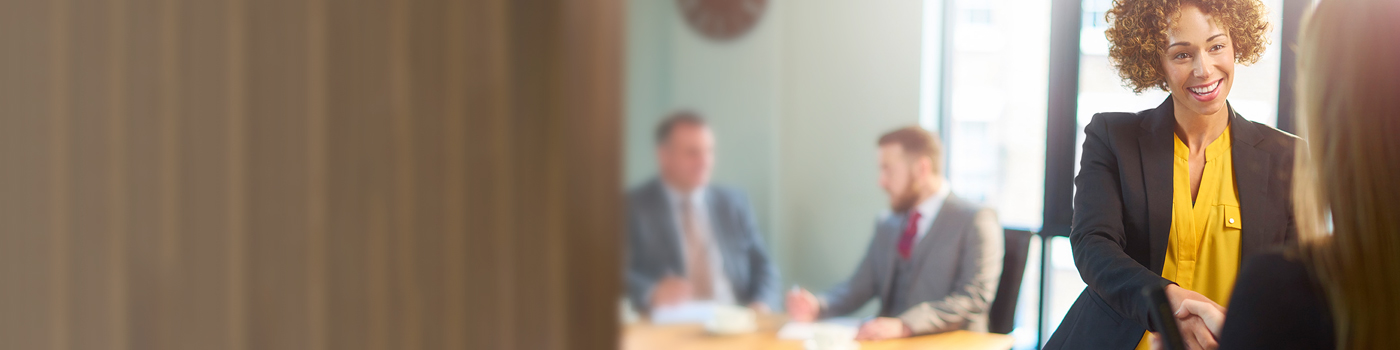 Two women shaking hands against a blurred background with suited men sitting around table