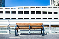 Wooden bench on road in-front of office building