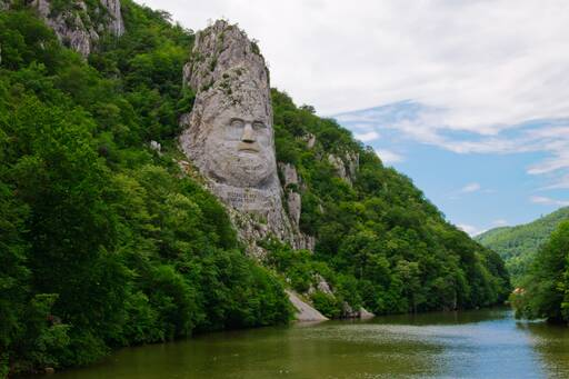 Face carved on mountain around water,Romania