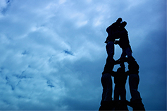 Human pyramid against a cloudy blue sky