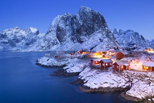 Lighted houses on snow covered mountains during sunset, Norway