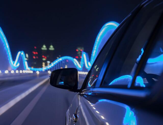 Rear view mirror of car on an illuminated bridge
