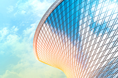 Reflection of sky and clouds in glass spiral wave with bend facade windows