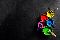 Five coloured paint buckets and brushes on a black background