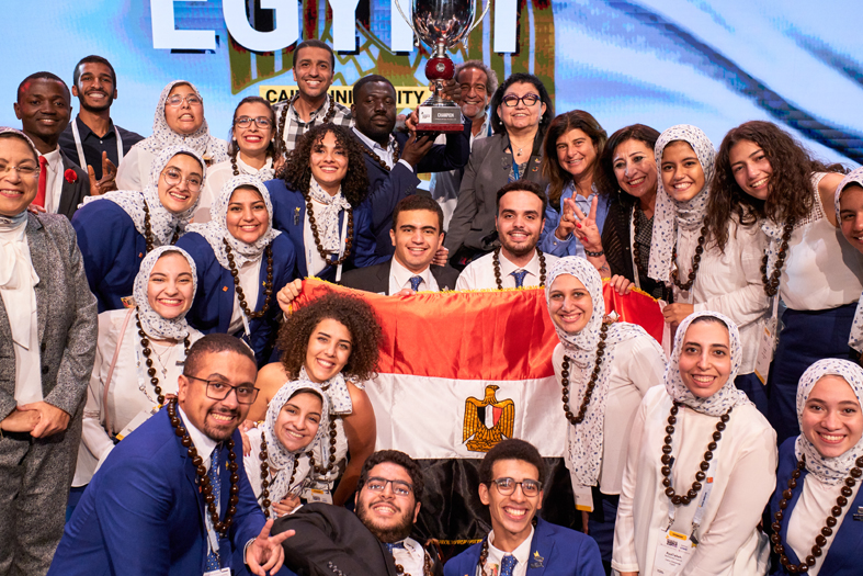 Group of people wearing formals and holding winning trophy & Egypt banner