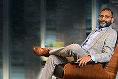 Harinder Takhar sitting on a brown wooden-finished chair