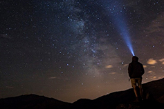 Man standing on a mountain and looking up with a head torch in night sky filled with stars