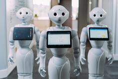 Three high tech white human robots with screen
