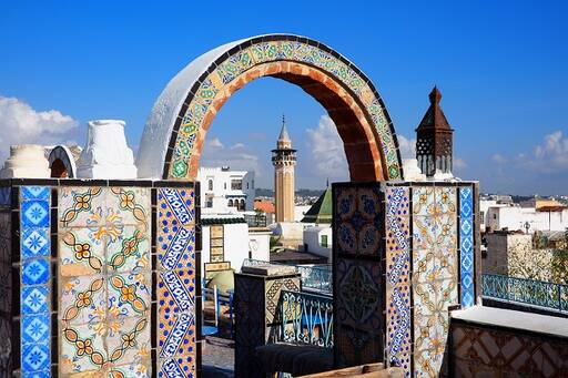 Entrance to mosque with colorful mosaic tiles in an archway.