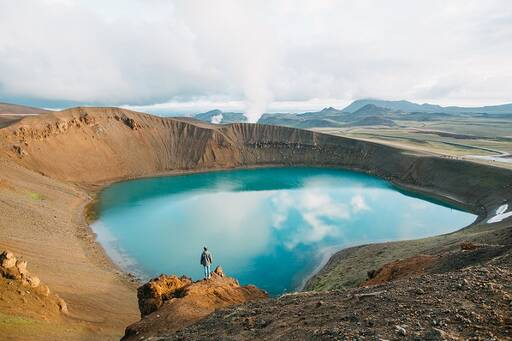Man looking down onto clear blue volcano lake.