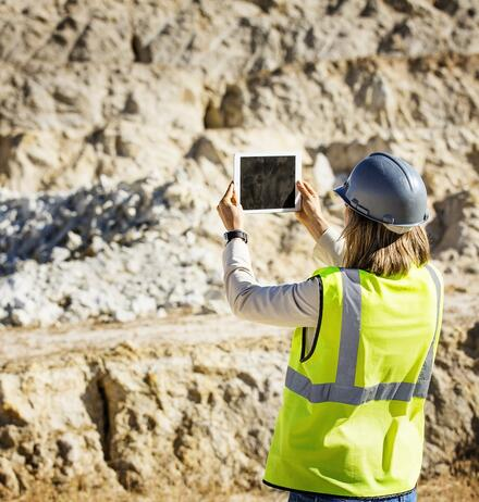 Female architect taking photograph on tablet with both hands