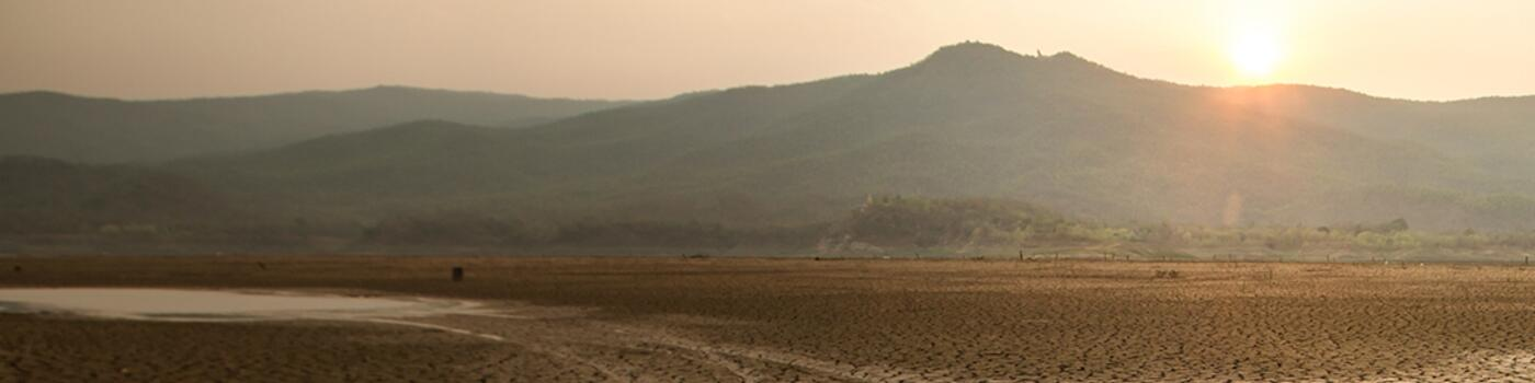 Barren land with cracks with mountains and sunset in background