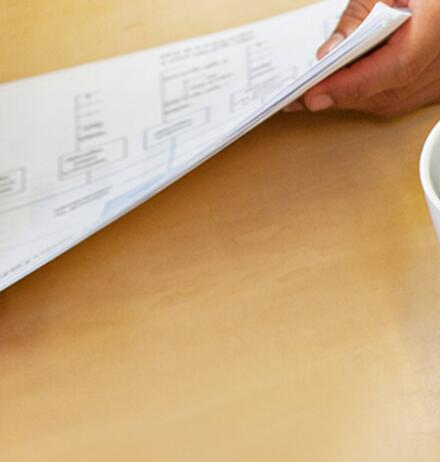 Hands of two people holding paper and coffee on table