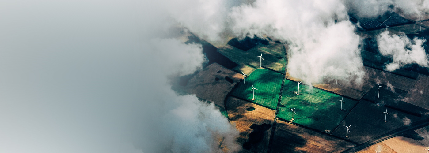 Top-view of green windmill field and clouds