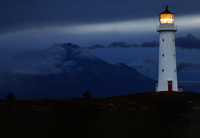 White lighthouse building in night, hills