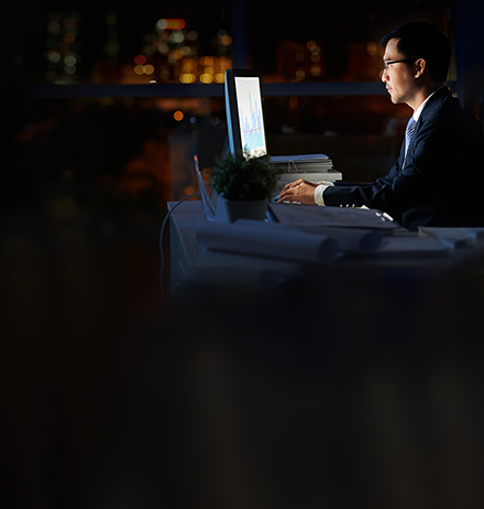 Man wearing business suit and spectacles, working on computer in office at late night