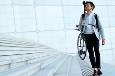 Man wearing blazer shows holding bicycle beside stairs