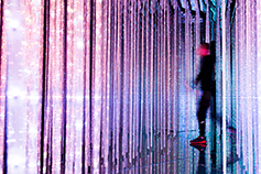 A man walks through a brightly lit data facility