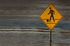 Pedestrian walking sign board half submerged in water