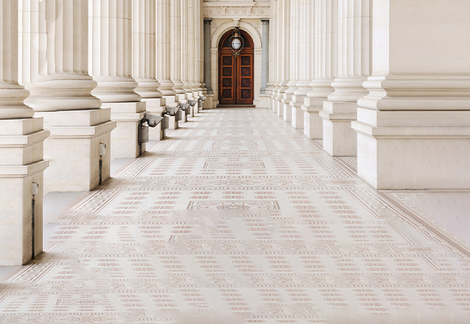 Architectural columns of Victorian Parliament building hall leading to gate