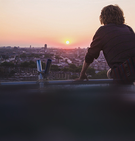 Man looking at a city and early morning sun-rise