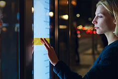 Woman at night using touch screen board