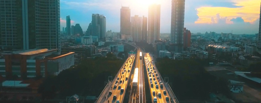 Buildings road bridge with cars driving into sunset