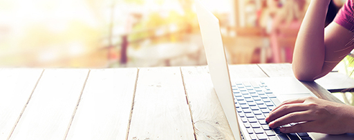 Person sitting at an outdoor table using a laptop