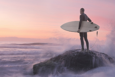 Man standing on cliff with surfboard