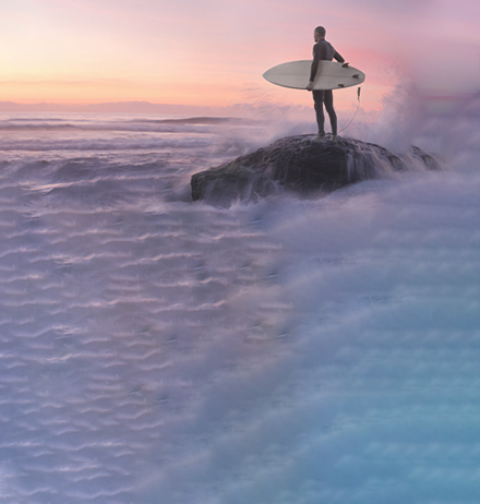 Man standing on a cliff with a surfboard