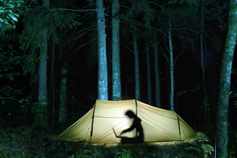 Person working insight a tent at night
