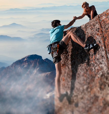 Woman helping man climbing mountain