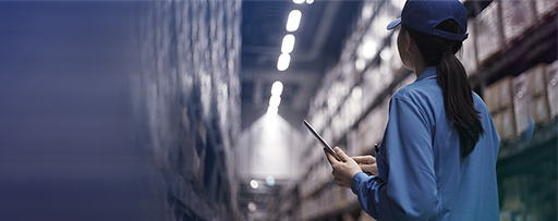 Female warehouse worker using digital tablet in logistics warehouse