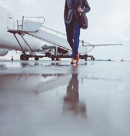 Man walking on runway with private jet in background