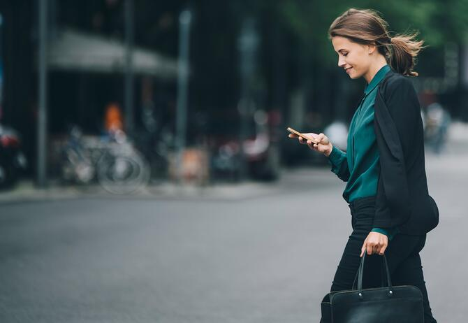 Woman checking phone while walking down the road