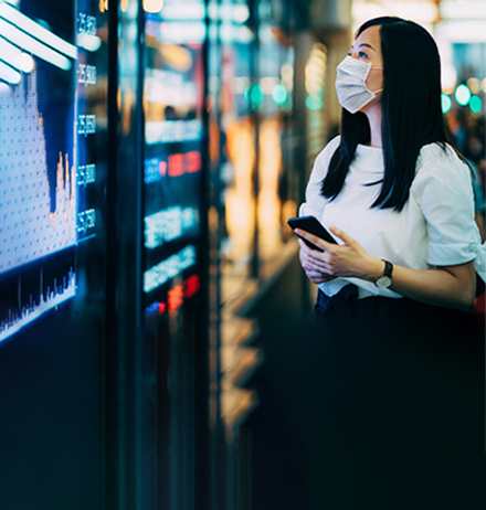 Woman in mask looking at stocks on digital screen